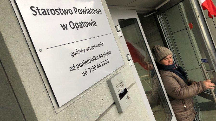 Estetyczna tabliczka informuje o godzinach pracy Starostwa Powiatowego w Opatowie.
